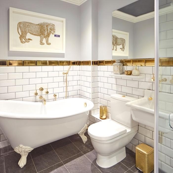 salle de bain moderne aux éléments traditionnels avec un revêtement mural de carrelage à imitation briques blanc et or, baignoire blanche autonome sur plancher gris
