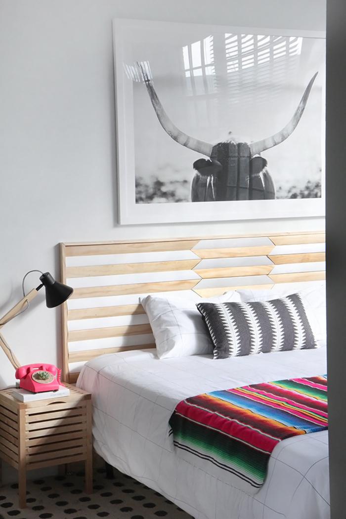 les motifs géométriques sur le textile et la tete de lit bois créent une ambiance moderne et chic dans la chambre à coucher