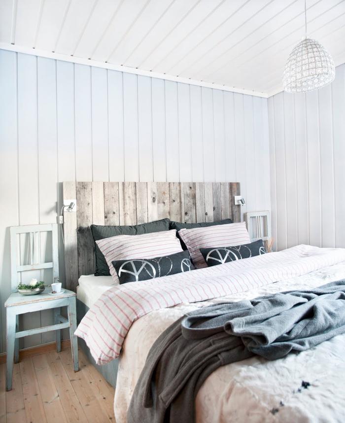 chambre à coucher d'ambiance rustique sereine revêtue de lambris qui contraste avec la tete de lit bois brut