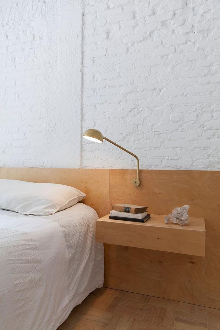 ambiance monochrome et épurée dans une chambre à coucher qui joue sur le contraste des murs en briques blanches et la tete de lit bois
