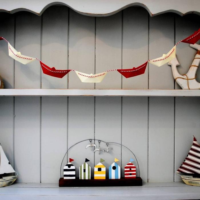 idée originale pour une déco origami destinée la chambre d enfant, jolie guirlande en bateaux rouge et blanc sur un fond en bois gris