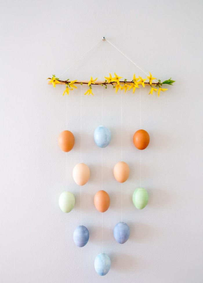 deco murale en branche fleurie avec des oeufs colorés vidés suspendues, activité manuelle paques