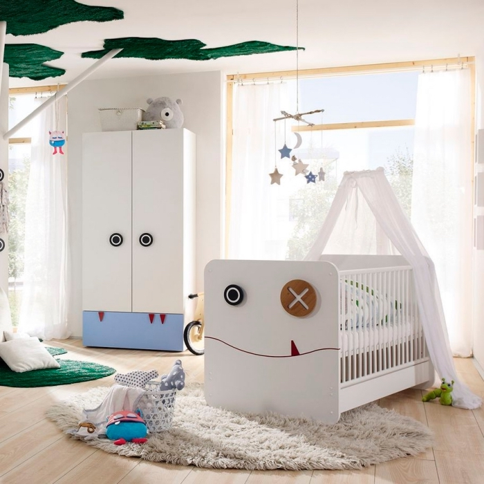 chambre bébé garçon au plafond blanc avec décoration verte et plancher de bois clair couvert de tapis moelleux blanc