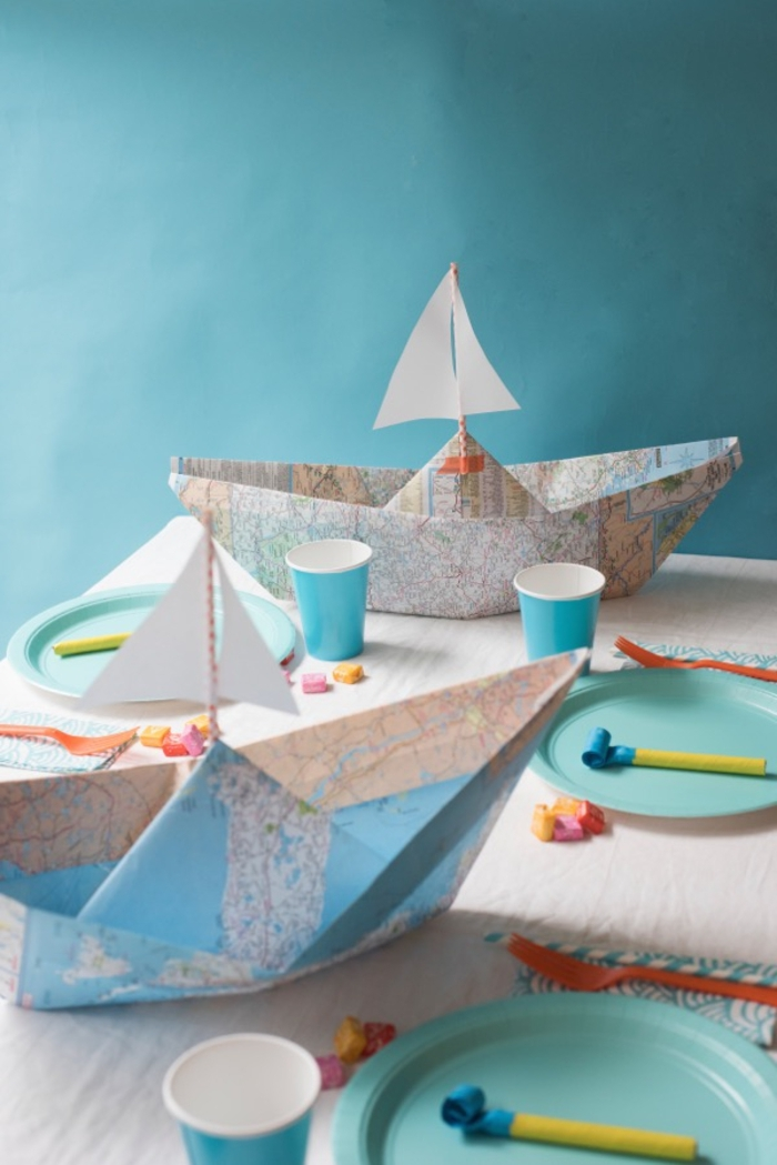 une déco de table qui fait voyager les invités avec sa déco origami en bateaux réalisés avec des cartes routières