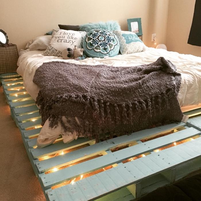 lit palette, lit cocooning, plaid de lit gris, coussins, mur couleur pêche