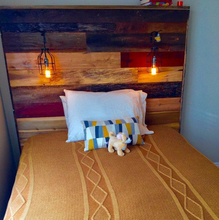exemple de tete de lit en palette de bois avec des lampes style industriel, couverture de lit orange, oreillers blancs et coussin coloré