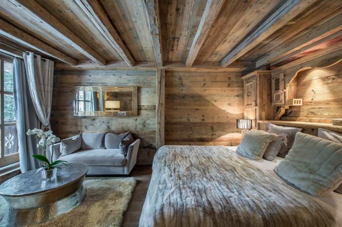 chamet moderne, plafond en bois, table ovale en métal, coussins gris moelleux, grande fenêtre