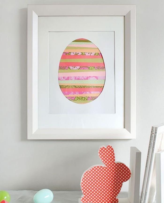 cadre blanc decoratif avec oeuf de paques coloré en bandes de papiers colorées à motifs divers, bricolage de paques original