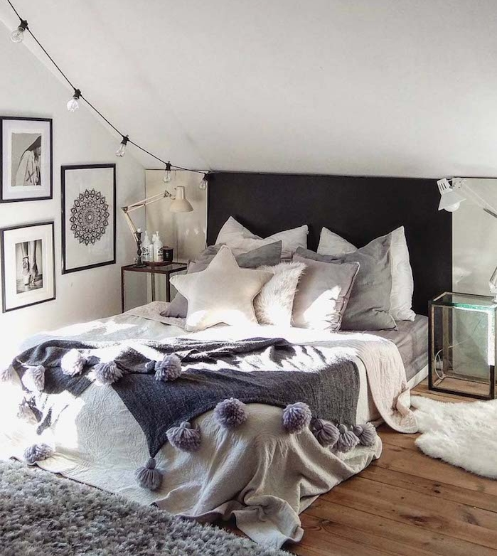 idee deco tete de lit noire avec guirlande d ampoules electriques, linge de lit gris et blanc, parquet en bois, tapis gris, coussins décoratifs