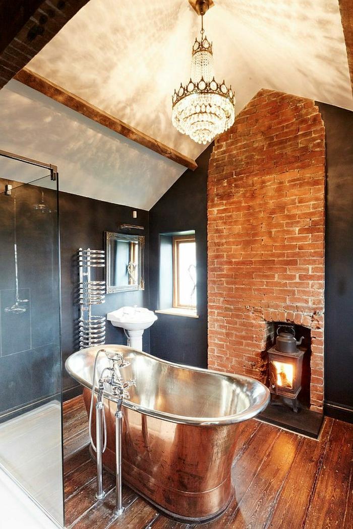 joli plafonnier dans la salle de bain, poêle scandinave, mur en briques, baignoire en fonte