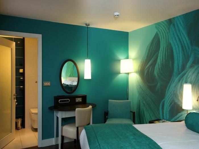 murs bleus avec une peinture abstraite, petite coiffeuse et miroir ovale, chaise turquoise, lampes romantiques, décoration murale unique