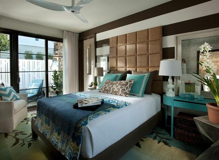 tapis à motifs floraux, tête de lit haute, bureau turquoise, grande fenêtre, fauteuil crème, coussins turquoises