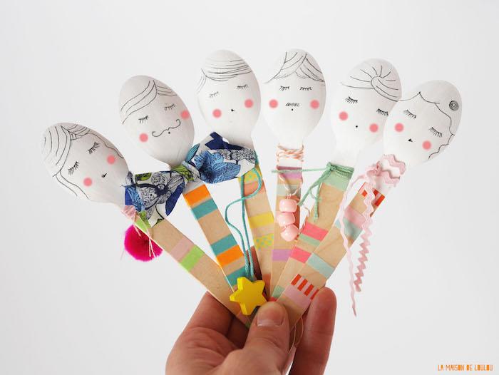 exemple d'activité manuelle maternelle, des cuillères décorées aux visages dessinés et corps à bandes colorées avec des chutes de tissu