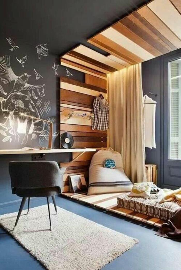 murs en gris perle avec des dessins arbres et oiseaux en blanc, déco chambre étudiant, amenager studio 15m2, petit tapis rectangulaire avec une chaise grise dessus, murs et plafond autour de la partie lit revêtus de bois couleur beige et marron