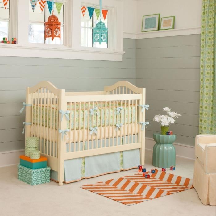 comment combiner les couleurs vert et orange dans la chambre bébé unisexe avec lit à barreaux beige et fauteuil beige