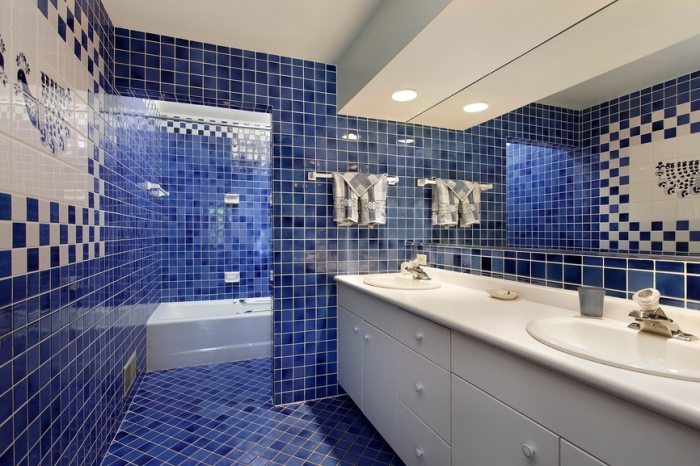 carrelage blanc et bleu foncé dans une salle de bain moderne avec éclairage led et meubles blancs, baignoire blanche et carrelage bleu marine