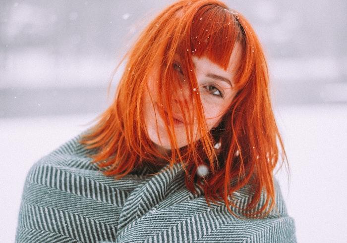 coupe de cheveux originale en carré long avec coloration cuivré, frange sur le front, cheveux effet décoiffé, paysage hiver