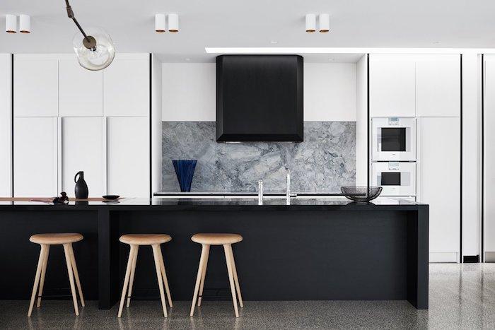 cuisine blanche et grise avec credence couleur grise, ilot central noir, armoires blanches, sol gris tabourets de bar en bois, exemple nuance de gris