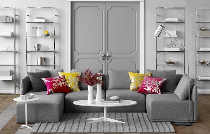 murs décorés de peinture gris clair, canapé gris, coussins framboise et jaunes, parquet marron, etageres metalliques, table basse blanche