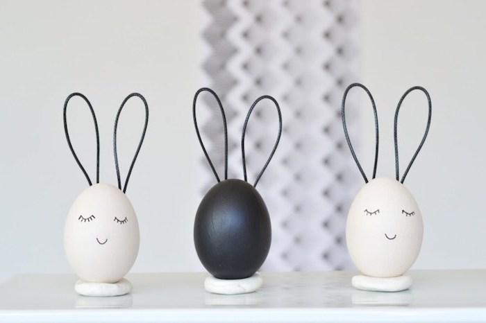 lapins de paques en oeufs colorés en blanc et noir avec des oreilles en elastique, activité créative adulte