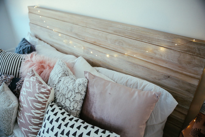 idée simple pour fabriquer une tete de lit en bois avec decoration en guirlande lumineuse, multitude de coussins deçoratifs en rose, blanc, noir et gris pour une ambiance cocooning