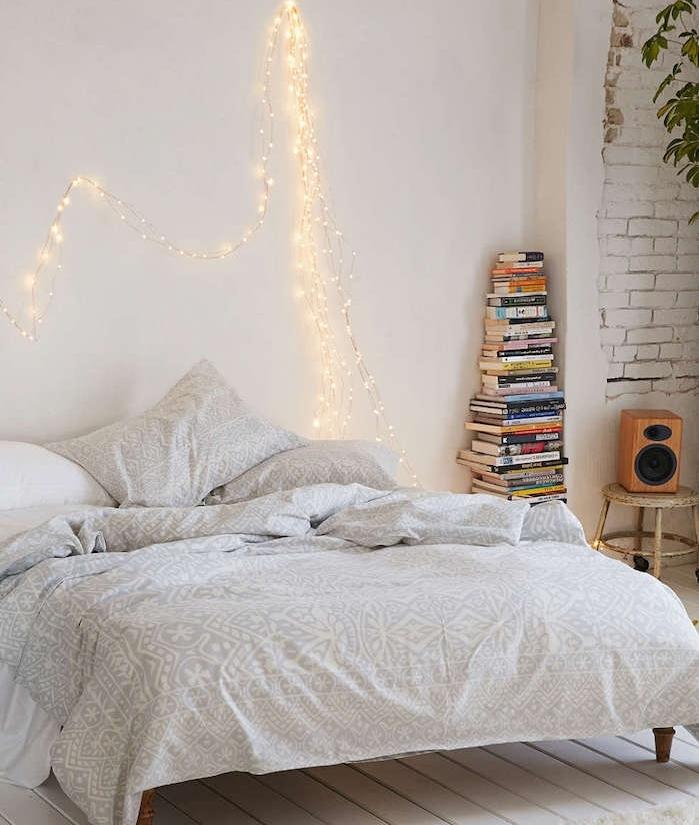 les astuces pour faire une tete de lit, version lumineuse, linge de lit gris et blanc, parquet blanchi, pile de livres, mur en briques blanches apparente