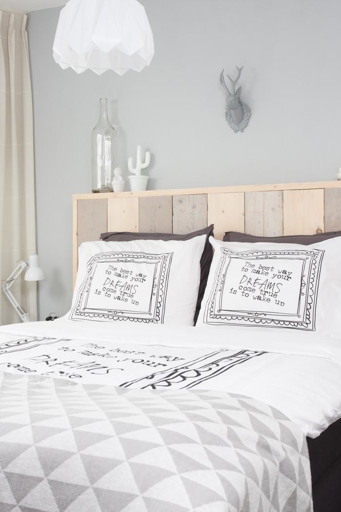 une chambre à coucher douce en gris et blanc avec une tete de lit bois naturel surmontée d'une trophée de chasse décorative ultra tendance