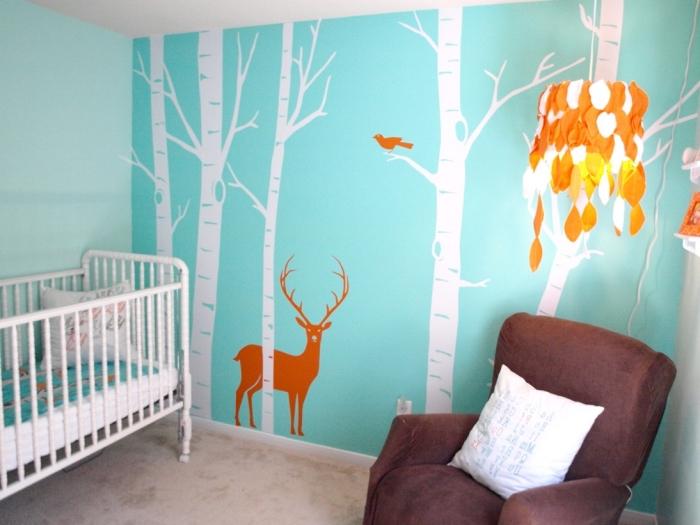 papier peint de nuance turquoise avec dessin à design forêt aux arbres blancs et animaux, fauteuil en velours marron avec coussin blanc