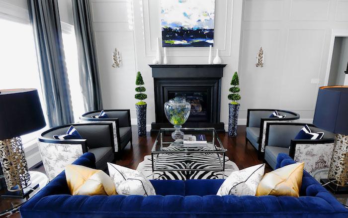 fauteuils et rideaux gris, canapé bleu marine, parquet marron foncé, mur couleur blanche, cheminée noire, quelle couleur avec le gris