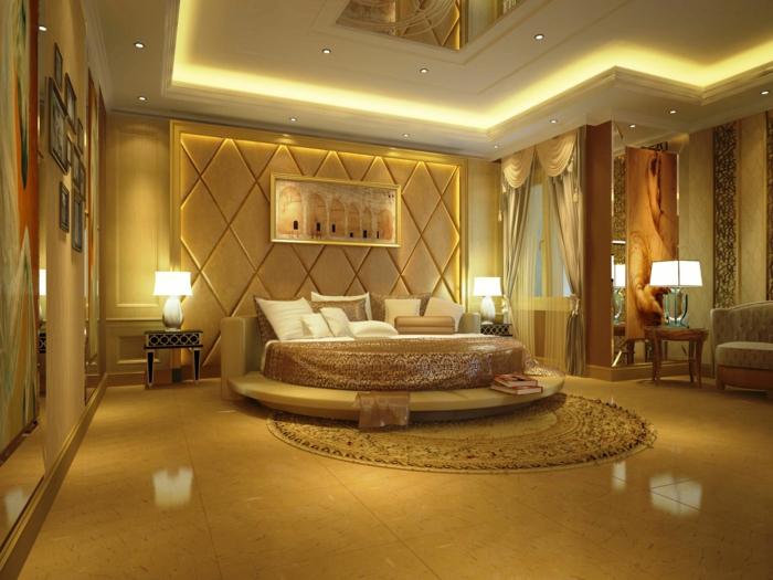 grand lit rond, tête de lit capitonnée, faux plafond avec éclairage, chambre de luxe et decoration murale couleur ocre