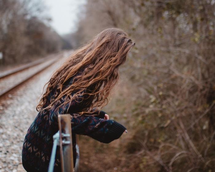 comment s'habiller pour une promenade en nature avec un pull oversize de couleur noire et à design géométrique, couleur de cheveux naturelle aux reflets cuivrés