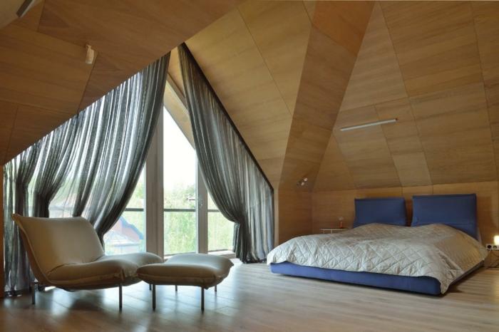 comble aménageable, lit bas, sol en bois, chaise et tabouret beige, rideaux gris transparents, revetement mural bois
