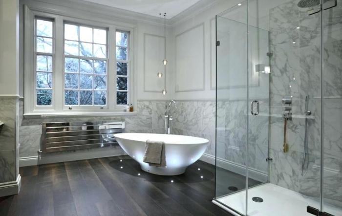 design luxueux et sophistiqué dans une salle de bain aux murs à design marbre blanc gris avec baignoire autonome et éclairage led sur le plancher