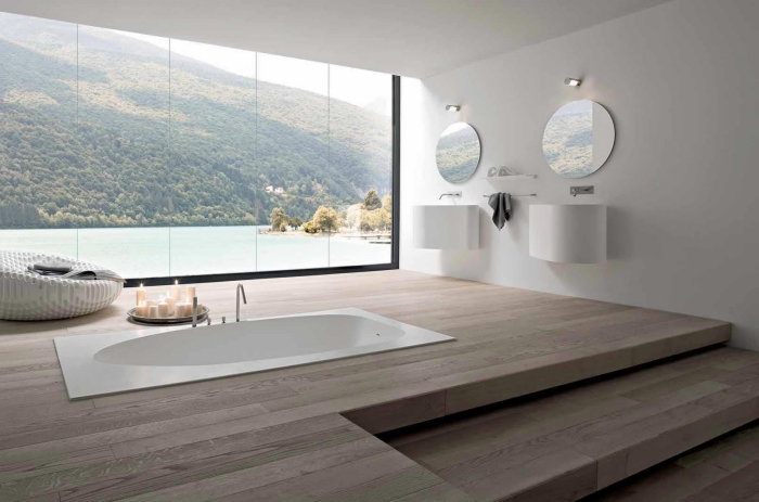 aménagement de la salle de bain spacieuse avec grande fenêtre, baignoire blanche incrustée dans le sol de bois clair