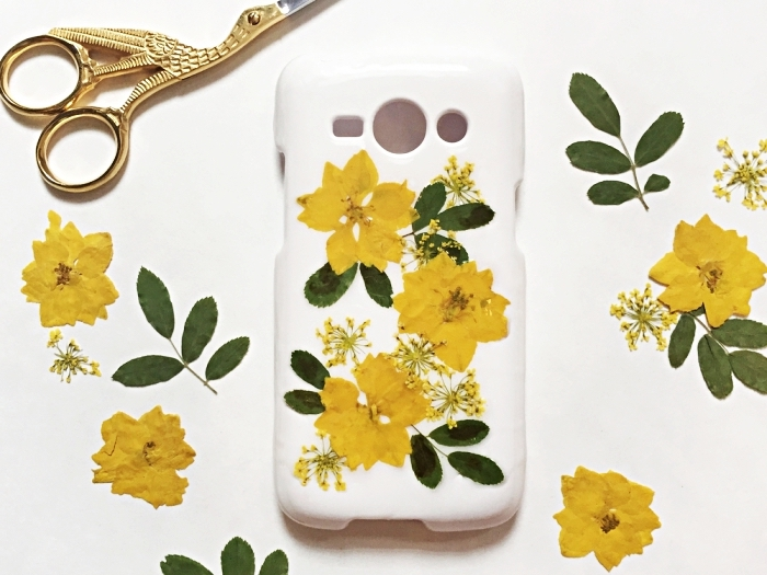 exemple de coque personnalisée facile avec fleurs jaunes et feuilles vertes séchées collées sur une coque blanche