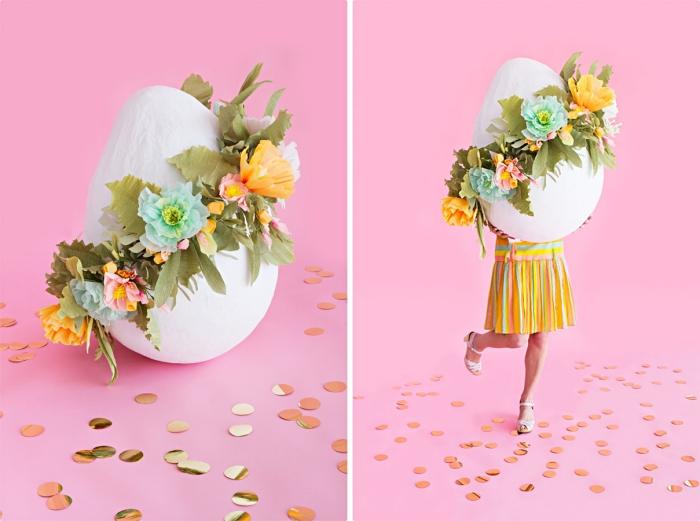 deco de paques amusante, modèle de faux oeuf gigantesque avec couronne florale en papier et tissu, fille habillée en robe multicolore à design rayé