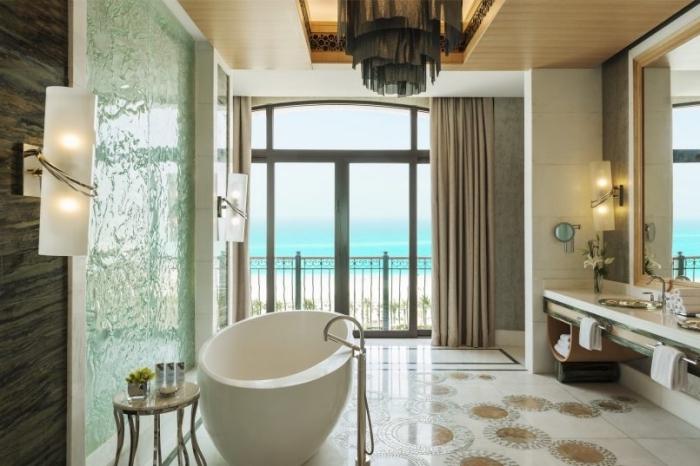 salle de bain moderne au carrelage de plancher blanc à motifs géométriques ronds marron et plafond de bois clair avec lustre noir