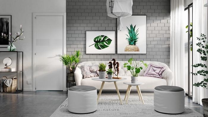 murs en briques peinture gris perle avec cadres decoratifs accents de végétation verte, canapé blanc, tables basses scandinaves et sol gris