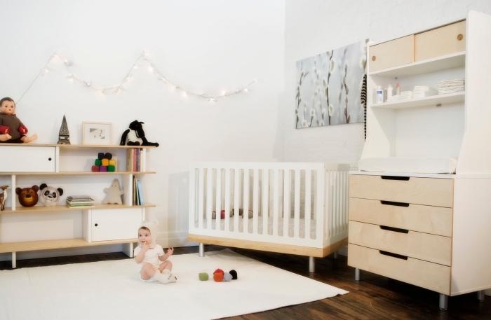 rangement horizontale avec étagères de bois et armoires blanches, idée déco chambre bébé aux murs blancs et parquet de bois foncé