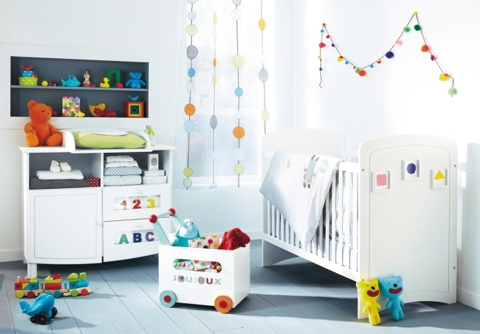 modèle parfait de la chambre complete bebe aux murs blancs décoré avec accessoires et jouets multicolore
