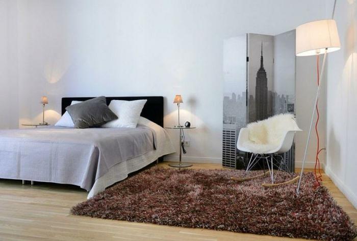 tapis marron, chaise scandinave, lit gris, plancher en bois, cloison amovible pliante