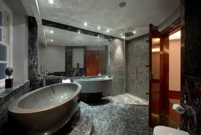agencement salle de bain de luxe, bagnoire ovale, éclairage au plafond, grand miroir nonencadré