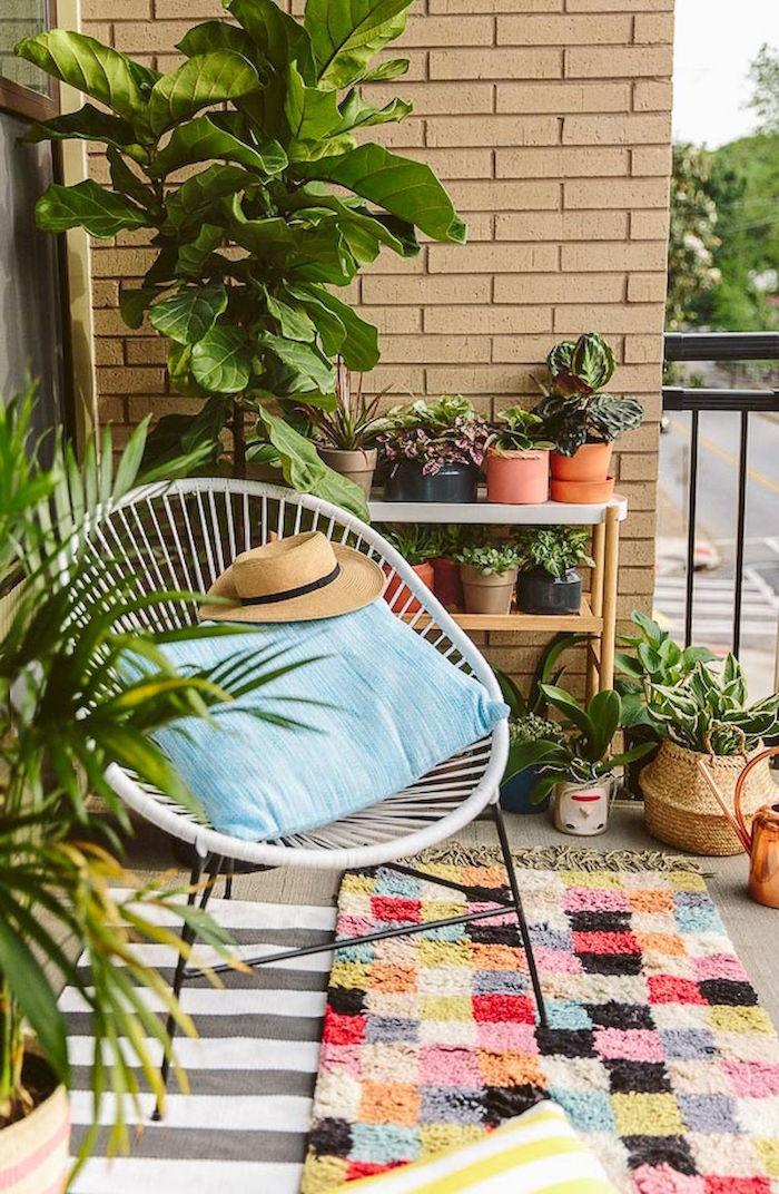photo de balcon décoré avec plantes et jardiniere, rocking chair blanc pour terrasse, tapis coloré balcons