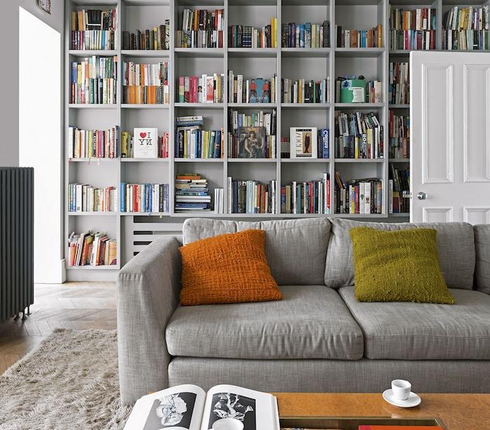 idée déco salon moderne avec frange bibliothèque grise coussin orange et vert, canapé gris perle, tapis gris moelleux, table basse en bois