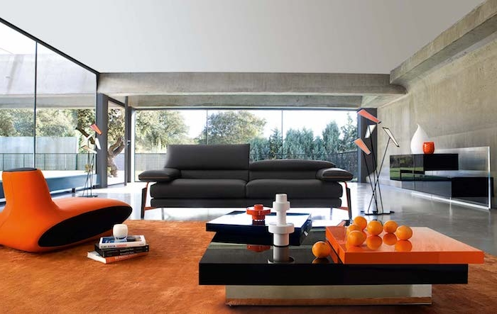 murs couleur taupe clair, tapis et fauteuil design couleur orange, table basse moderne noir et orange, canapé couleur gris anthracite