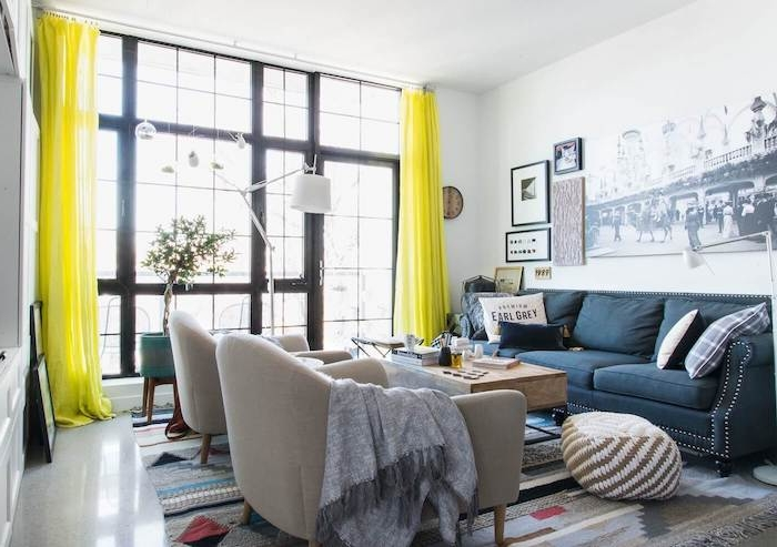 amenagement salon moderne avec fauteuils nuance gris, canapé bleu foncé, tapis gris à motifs géométriques, rideaux jaunes, deco mural photo noir et blanc