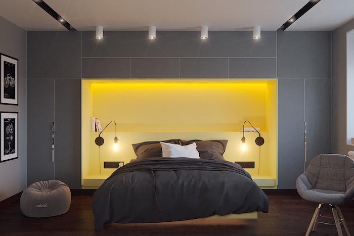 mur couleur gris anthracite avec une niche murale jaune et parquet marron foncé, chaise et pouf gris, linge de lit gris