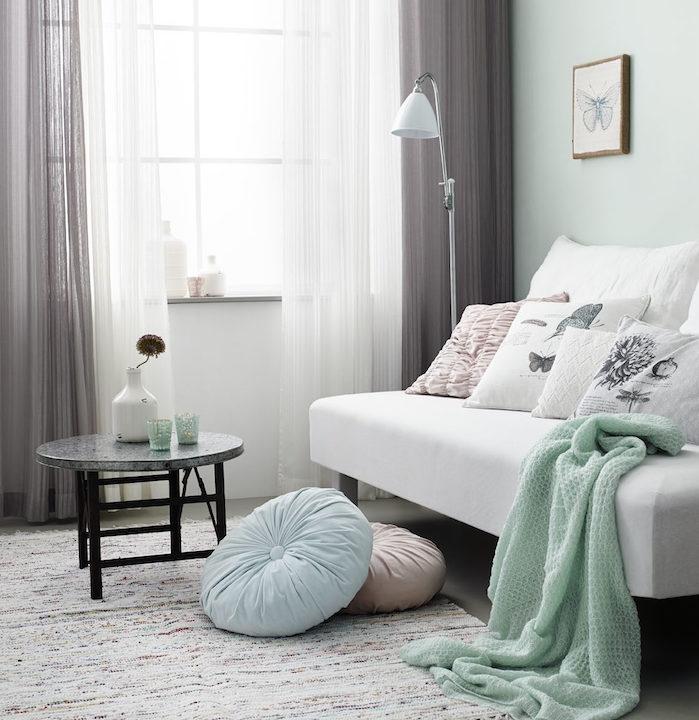 idée association de couleur avec le gris, rideaux gris et blanc, canapé blanc, plaid vert celadon, table basse minimaliste, coussins décoratifs, mur peinture vert clair