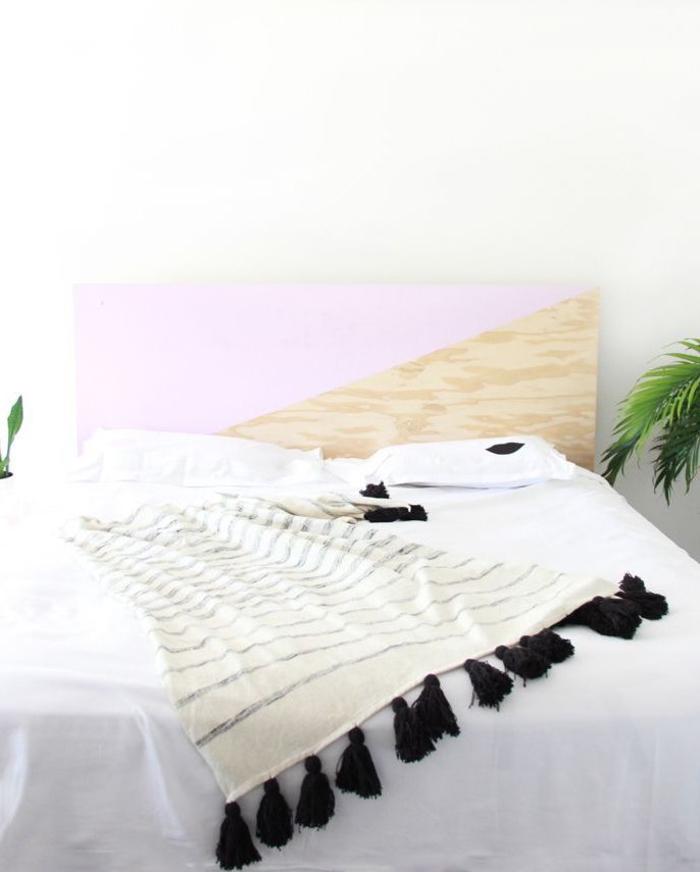 ambiance scandinave moderne dans une chambre à coucher cocooning meublé d'une tete de lit bois à motif géométrique crée avec de la peinture rose pastel