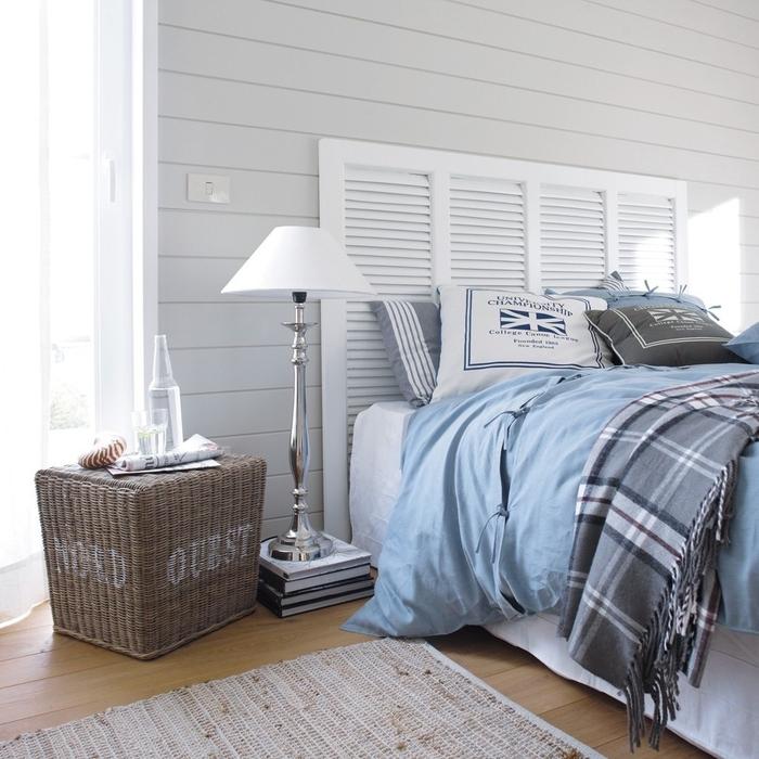 ambiance sereine avec un lambris blanc et une tete de lit bois récup dans une chambre à coucher de style bord de mer